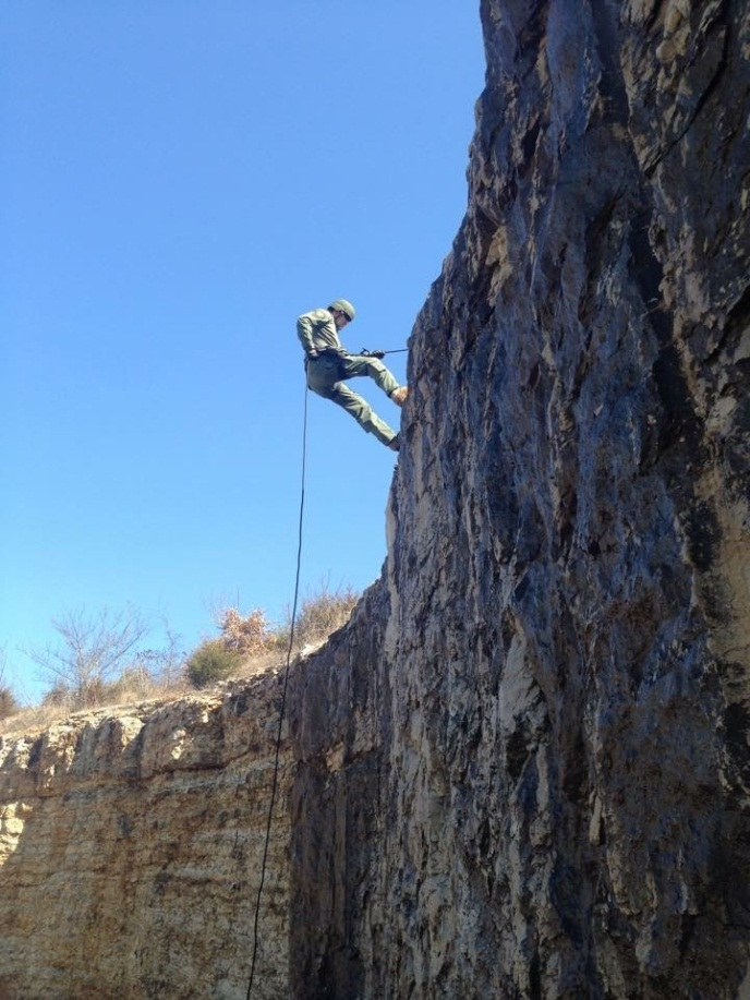 TACTICAL TEAM RAPPELLING DOWN ROCK WALL