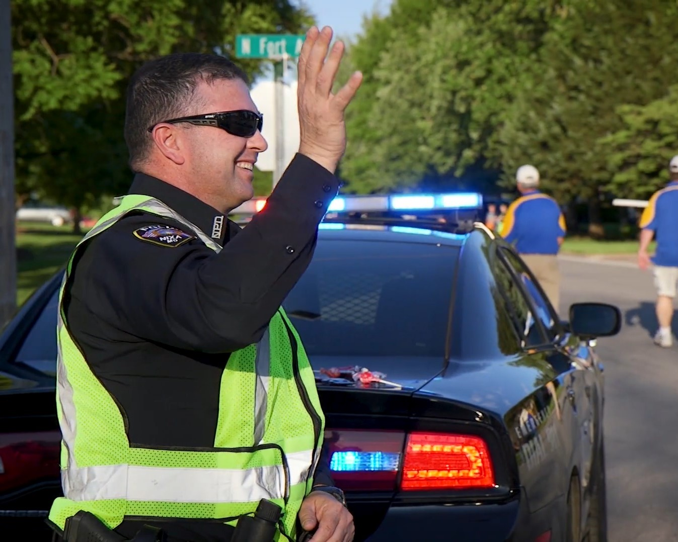 OFFICER WAVING DURING PARADE DETAIL
