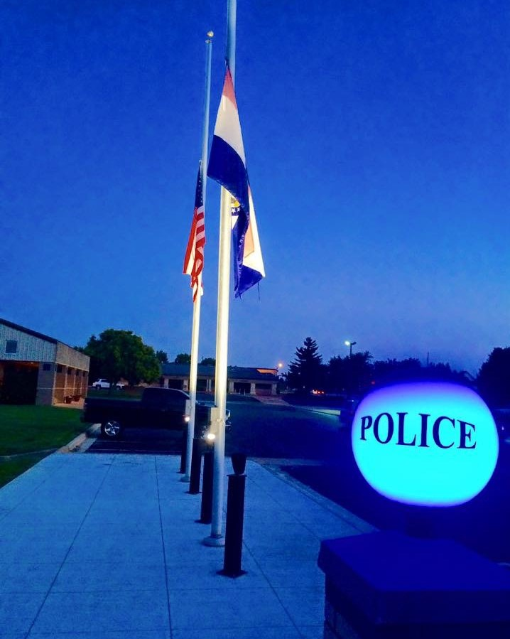 BLUE POLICE LIGHT NEAR FLAGS
